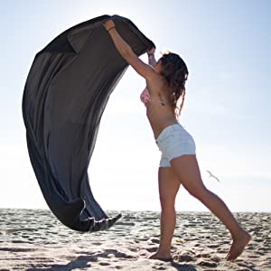 5 Best Blankets for Camping woman spreading blanket on the beach